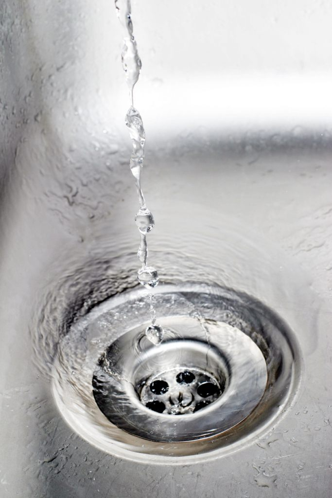 a plumber cleaning clogged pipes in Chesapeake, VA