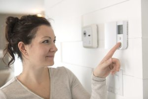 a woman is using a thermostat to turn on her air conditioner in Chesapeake, VA