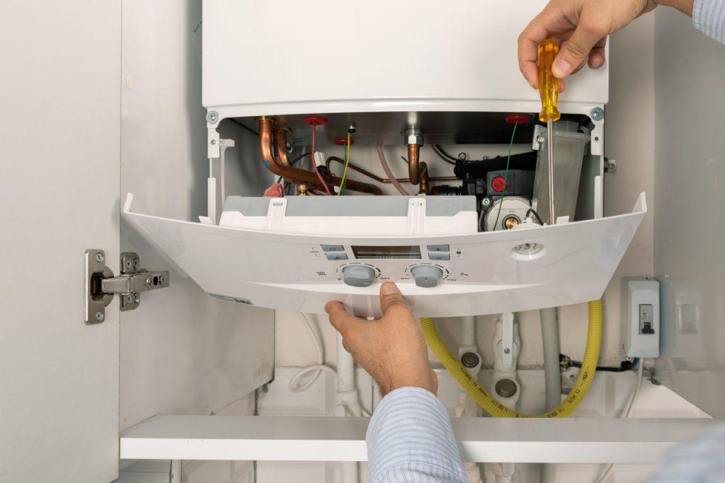a plumber repairing a heating boiler in Virginia Beach, VA